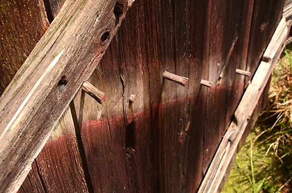 """En av """"zäta""""listerna på dörren har lossnat och man ser att även dörren är sammanhållen av små träplugg. Men gångjärnsbeslagen är smidda."""