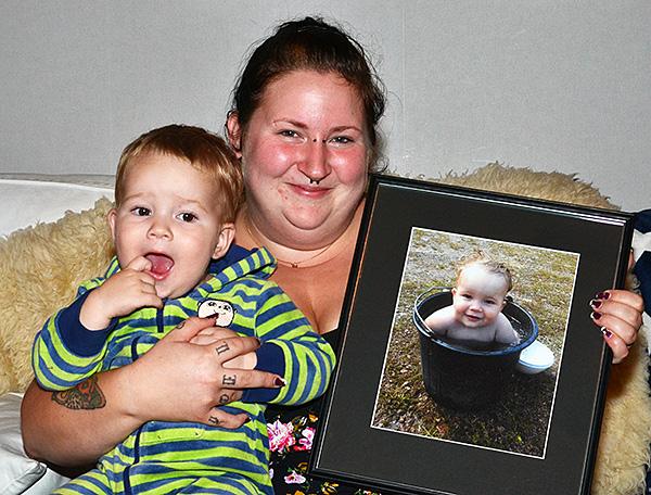Johanna Andersson med sin inramade förstoring på vinnarbilden. Sonen Joel trivs lika bra i mammas famn som i vattenhinken.