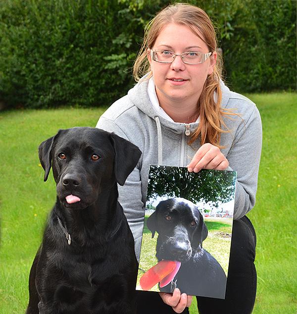 Josefine Johansson med sin förstoring på hunden Abbe. Det kan inte hjälpas att tungan halkar ut lite när Abbe ser bilden och tänker på sommarens isglass.